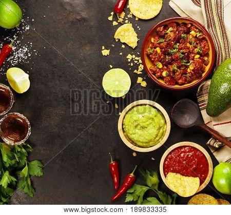 Mexican food concept: tortilla chips, guacamole, salsa, chili with beans, tequila shots and fresh ingredients over vintage rusty metal background. Top view