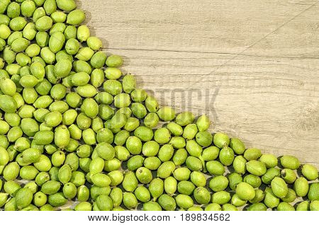 Green young walnuts in husks on wooden table