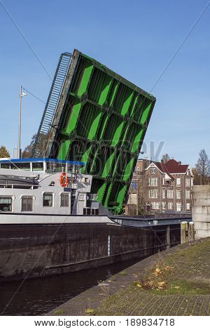 Green drawbridge with big boat under it in the day in Amsterdam