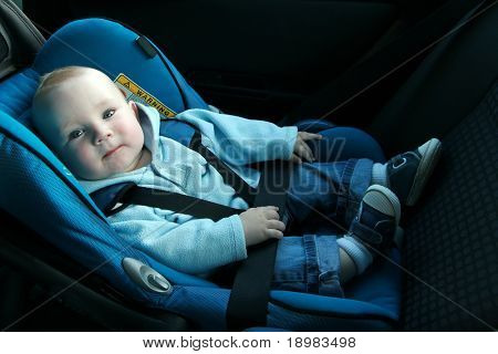 7 months old baby boy in a safety car seat. Safety and security