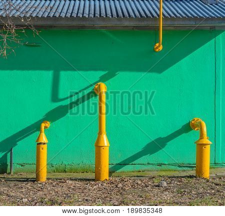 Yellow gas pipes in front of green building wall. Fragment of gas distribution station