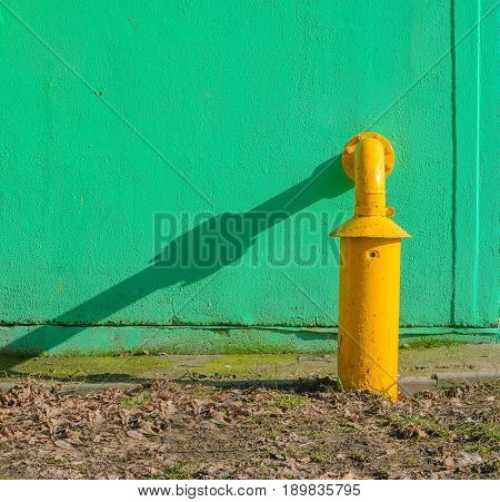 Yellow gas pipe in front of green building wall. Fragment of gas distribution station