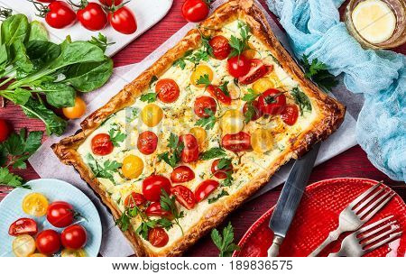 Deliciously simple tomato tart made with puff pastry, red and yellow cherry tomatoes, spinach and ricotta cheese.  Concept of healthy eating or vegetarian food. top view.