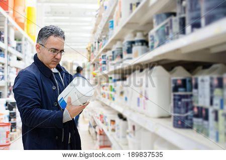 Man choosing paint on the shelves of a hypermarket shopping center hardware store