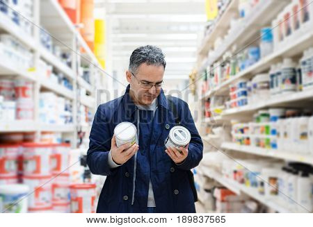 Man choosing paint on the shelves of a hypermarket shopping center hardware store