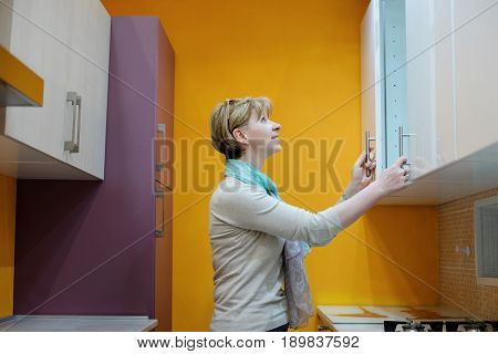 Beautiful smiling woman choosing the furniture kitchen in a mall shopping center