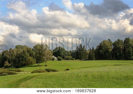 Green meadow before the manor of Mikhailovskoye village. State museum-reserve of A. S. Pushkin in Pushkinskiye Gory Pskov region Russia. Sunny summer day.