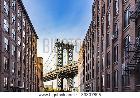 famous Manhattan Bridge with Empire State in the arch seen from a narrow alley enclosed by two brick buildings on a sunny day, New York City