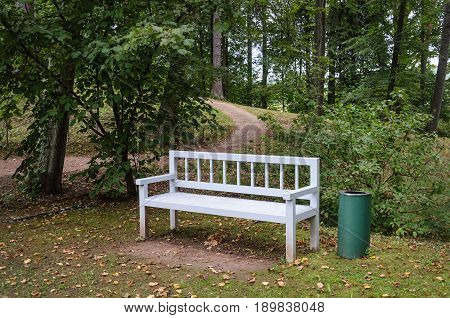 White wooden bench in old park of Trigorskoye village State Museum-reserve of A. S. Pushkin in Pushkinskiye Gory