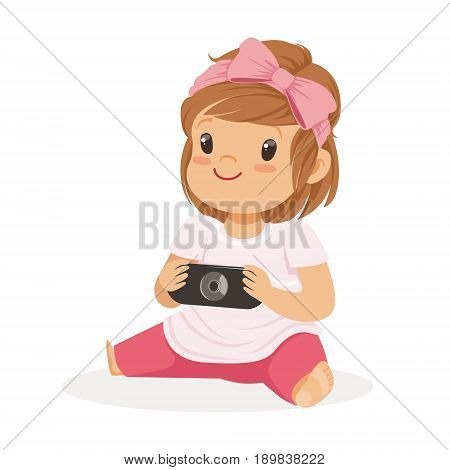 Cute little girl sitting on the floor and playing with camera, colorful cartoon character vector Illustration isolated on a white background