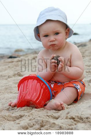 8 months old baby boy playing on a beach