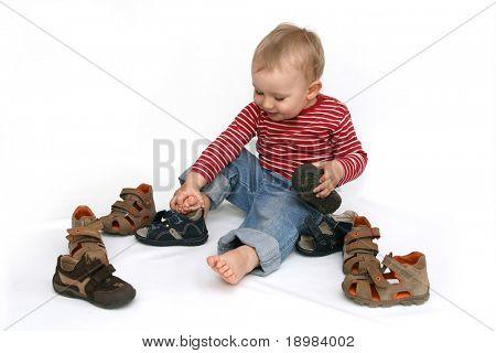 Kleines Kind versucht, auf seine Schuhe. Baby Boy mit Sommer-Schuhe in der Hand, isolated on White.