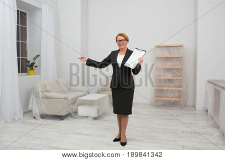 Apartment rent agreement. Realtor standing in the middle of the room with agreement in her hand. Woman in business suit standing in white living reoom.