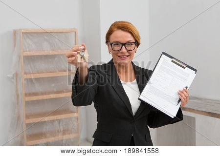 Realtor proposing to sign an agreement for apartment rent, camera focused on face. Woman realtor stnading in the room with keys and agreement in her hands.