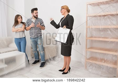 Real estate scammers with an estate agent. Couple arguing with an agent in the room with white walls and new furniture.