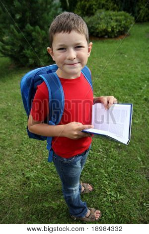 Boy ready for school with books and school backpack.