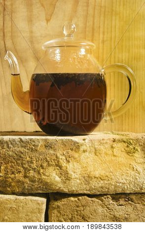 filled hot glass teapot on a wall and in front of a wooden wall
