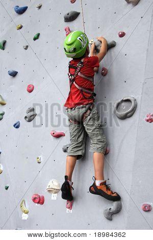 6 Jahre altes Kind Klettern an einer Wand in einem Kletter-Center.