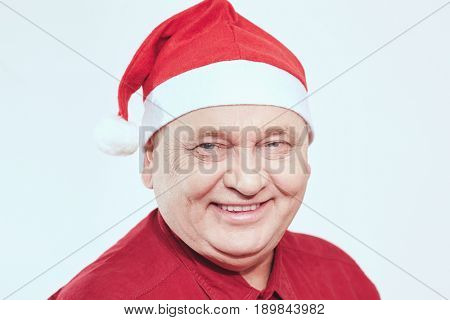 Portrait of smiling aged man wearing Santa Claus hat and red shirt against white background - Christmas concept
