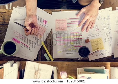 Student writing the lecture on wooden table
