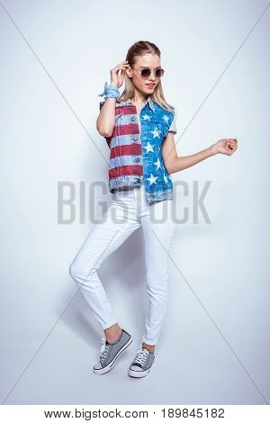 Attractive blonde girl wearing denim vest with us flag and posing in studio