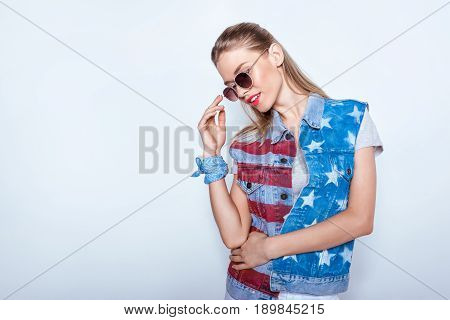 Smiling young woman wearing denim vest with american flag