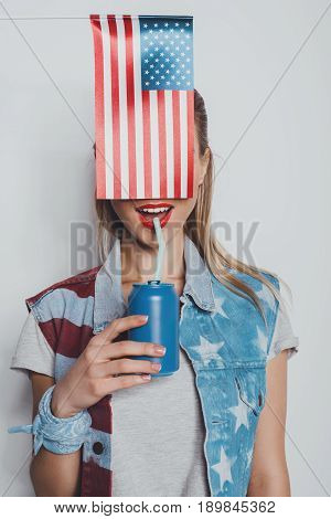 Cheerful Stylish Girl In American Patriotic Outfit Drinking Soda From Can, With American Flag In Fro