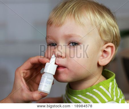 Catarrh - Mother spraying 2 years old baby boy medicine in nose, nose drops, nose spray.