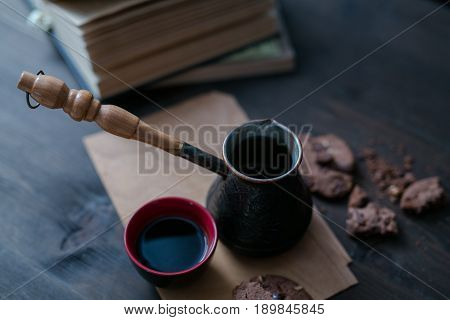 Coffee Cup And Cookies And Coffee Maker Are On The Wooden Table Next To The Book