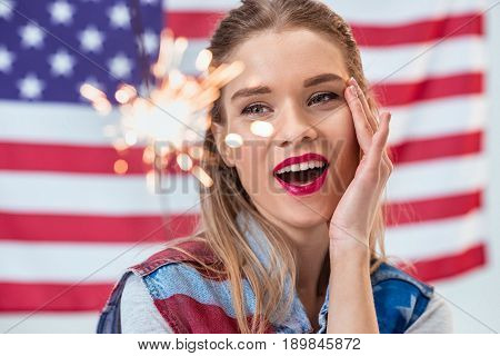 Portrait Of Happy Woman Holding Sparkler With American Flag Behind, Independence Day Concept