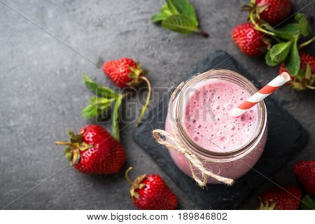 Strawberry milkshake or smoothie in glass jar on black slate background. Diet organic food. Top view copy space.