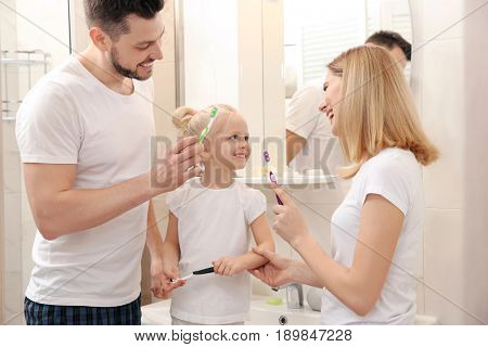 Young couple and their beautiful daughter brushing teeth near mirror in bathroom