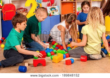 Children building blocks in kindergarten. Group kids playing toy on floor . Top view of interior preschool. Children develop their fingers in a game of cubes.