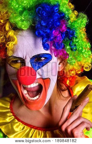 Evil clown on black background. Mad aggressive woman is smoking cigar and shout. Portrait of crazy female with an angry look after performance.