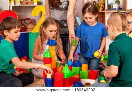 Children building blocks in kindergarten. Group kids playing toy on floor. Top view of interior preschool. Building a tower of cubes.