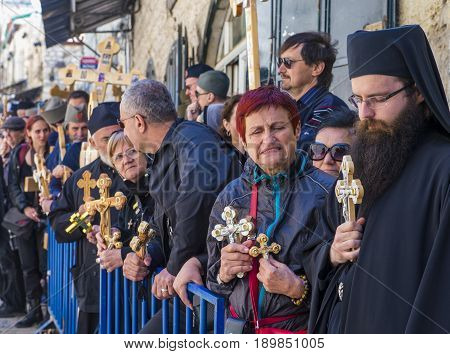 JERUSALEM - APRIL 14 : Christian pilgrims carry across along the Via Dolorosa in Jerusalem on April 14 2017 commemorating the path Jesus carried his cross on the day of his crucifixion