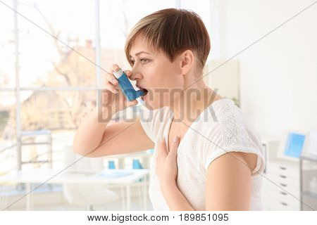 Adult woman using inhaler in clinic