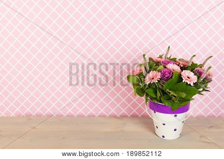 Colorful pink and purple bouquet in vase in interior