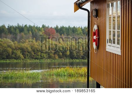 Yellow wooden house on stilts with a lifebuoy on a wall. Lake in the background