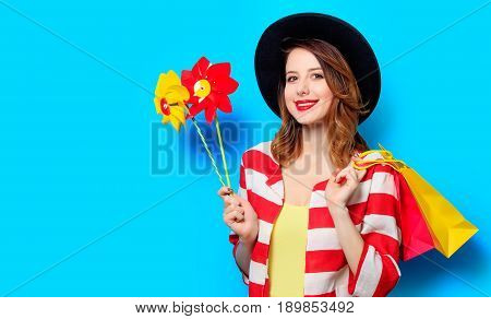 Woman With Pinwheels And Shopping Bags