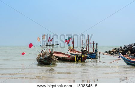 Small woodenl fishing boats (Longtail boats) anchored on beach in Thailand