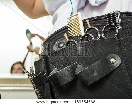 Hairdressing equipment concept. Professional hairdresser tools in black belt. Scissors combs and clips.