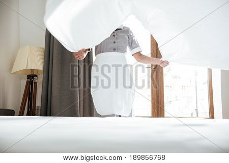 Cropped image of a hotel maid changing the bed sheets
