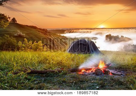 campfire and tent at sunrise. View of tourist tent on green meadow. Camping background. Adventure travel active lifestyle freedom concept. Summer landscape. Foggy meadow in the sunny beams