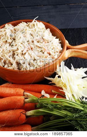 Healthy coleslaw cabbage salad in a bowl and carrots