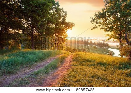 summer landscape road river forest. Sunrise. Foggy river with fresh green meadow in the sunny beams. Rural landscape of empty dirt road