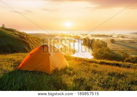 view of tourist tent on green meadow at sunrise or sunset. Camping background. Orange tent on the hill near the river. Adventure travel active lifestyle freedom concept. Foggy river in the sunny beams