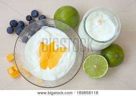 Yogurt dessert with mango fruit, blueberries and lime.