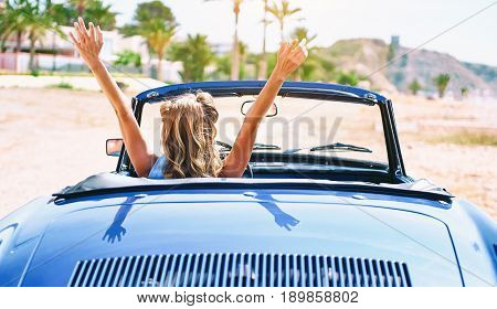 Woman with a hands raised sitting in retro cabriolet car. Back view
