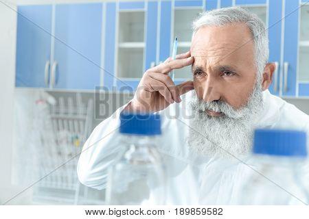 Thoughtful Senior Bearded Chemist In White Coat In Chemical Laboratory